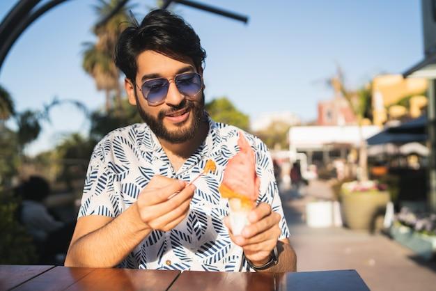 Hombre disfrutando el clima soleado mientras come un helado