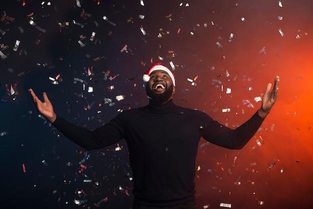Hombre disfrutando de confeti con los brazos abiertos