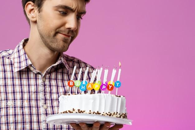 Hombre disgustado con pastel de cumpleaños con una vela no sople.