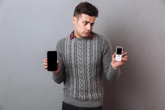Hombre disgustado en suéter eligiendo entre teléfonos inteligentes y mirando