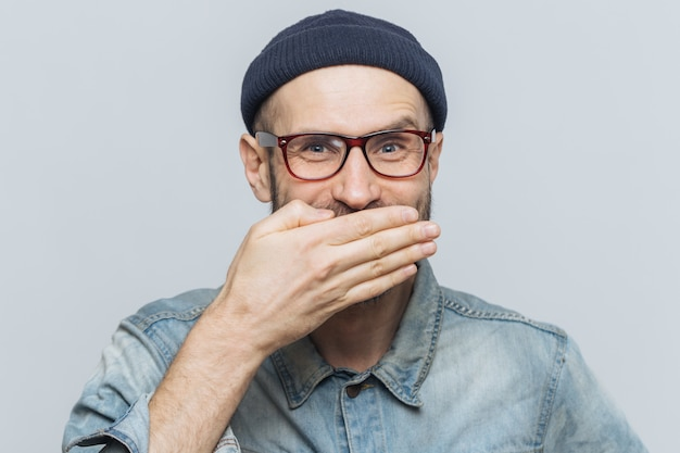 Hombre divertido con aspecto atractivo ríe o se ríe alegremente, se tapa la boca con la mano