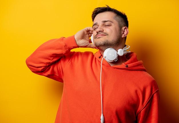 Hombre divertido con auriculares en pared amarilla