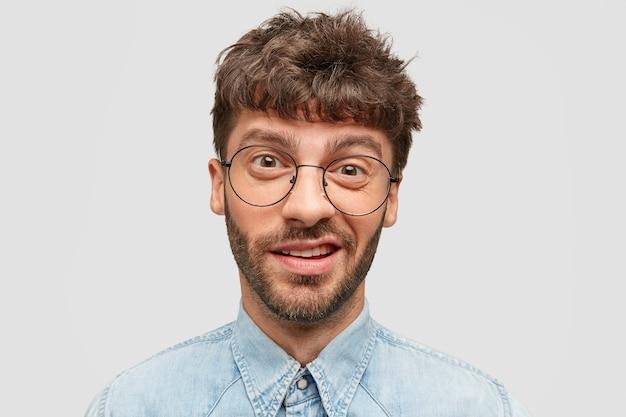 Hombre divertido con barba incipiente, tiene mirada indecisa y curiosa, frunce el ceño, mira directamente a la cámara, vestido con camisa de mezclilla, aislado sobre una pared blanca