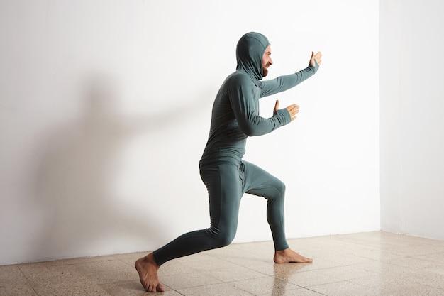 Hombre divertido barbudo posa como un ninja con su suite térmica de capa base térmica, aislado en blanco