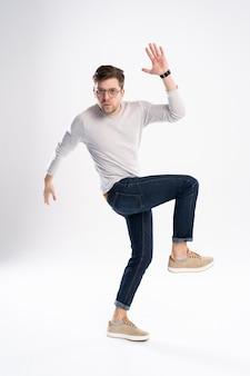Hombre divertido en camiseta casual y jeans saltando aislado sobre blanco