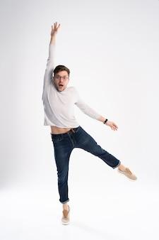 Hombre divertido en camiseta casual y jeans saltando aislado sobre fondo blanco.