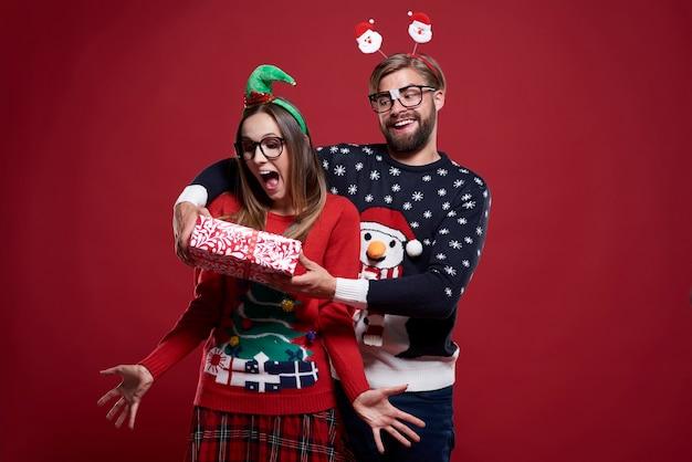 Hombre divertido dando el regalo de navidad pareja de pie junto al bastón de caramelo