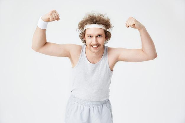 Hombre divertido demuestra bíceps, mostrando los dientes