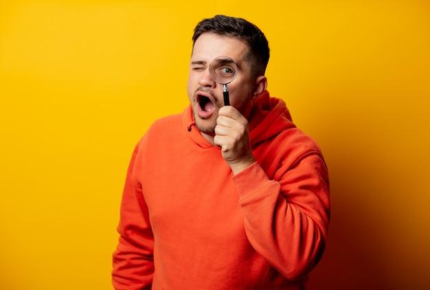 Hombre divertido con lupa en pared amarilla