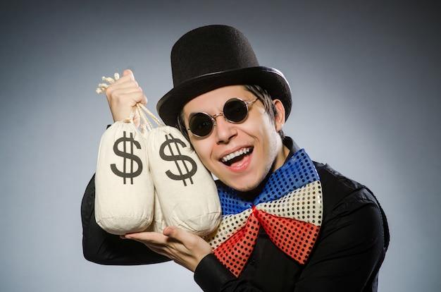 Hombre divertido con sacos de dólares de dinero