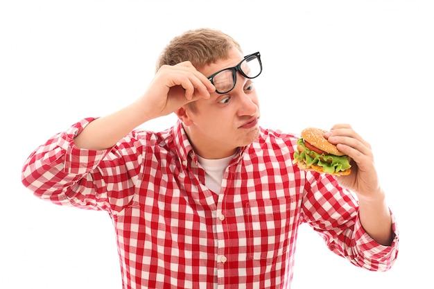 Hombre divertido en vasos comiendo hamburguesas aislado en un blanco