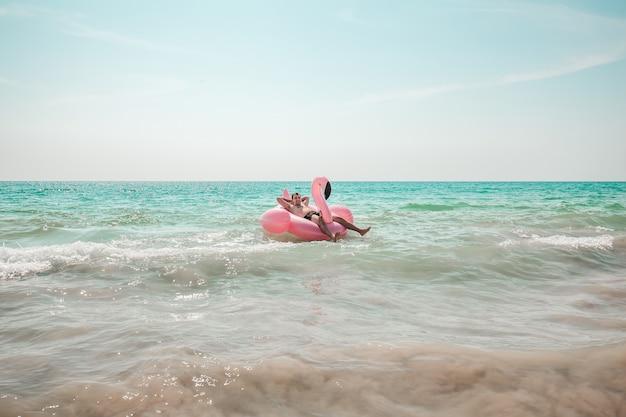 El hombre se divierte en el flotador de piscina inflable flamenco rosa