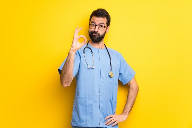 Hombre del doctor del cirujano que muestra una muestra aceptable con los dedos