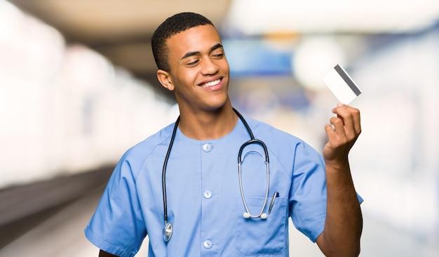 Hombre del doctor del cirujano que sostiene una tarjeta de crédito y que piensa en un hospital