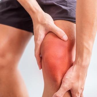 Hombre con dolor muscular sobre fondo gris. los ancianos tienen dolor de rodilla debido a la rodilla del corredor o síndrome de dolor femororrotuliano, artrosis, artritis, reumatismo y tendinitis rotuliana. concepto medico