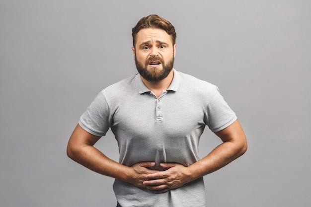Hombre con dolor sosteniendo su estómago dolorido i