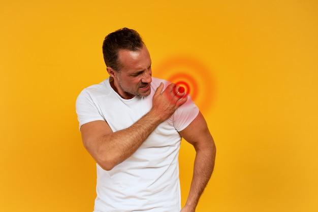 Hombre dolorido con dolor de espalda. fondo amarillo