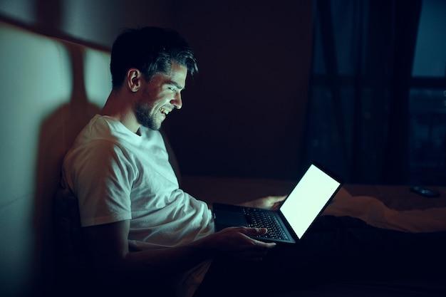 Un hombre en un dormitorio en casa frente a una computadora portátil viendo películas por la noche