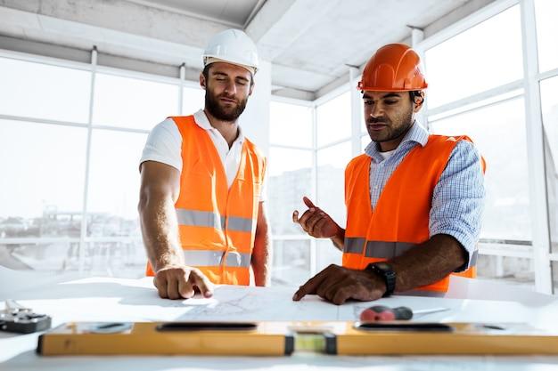 Hombre de dos ingenieros mirando el plan del proyecto sobre la mesa en el sitio de construcción