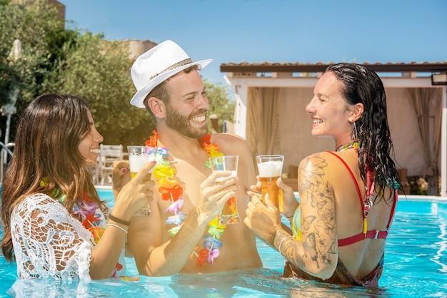 Un hombre y dos mujeres beben cerveza en la piscina divirtiéndose.