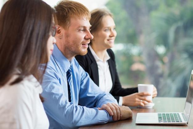 Hombre y dos mujeres mirando un portátil