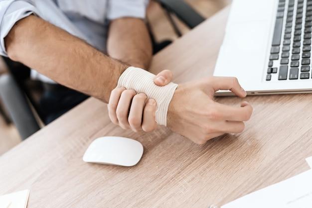 A un hombre le duele el brazo. le duele, sufre.