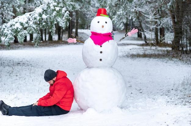 Un hombre duerme cerca de un gran muñeco de nieve en un bosque cubierto de nieve.