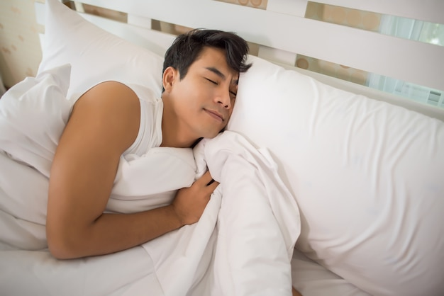 Hombre durmiendo en la cama por la mañana