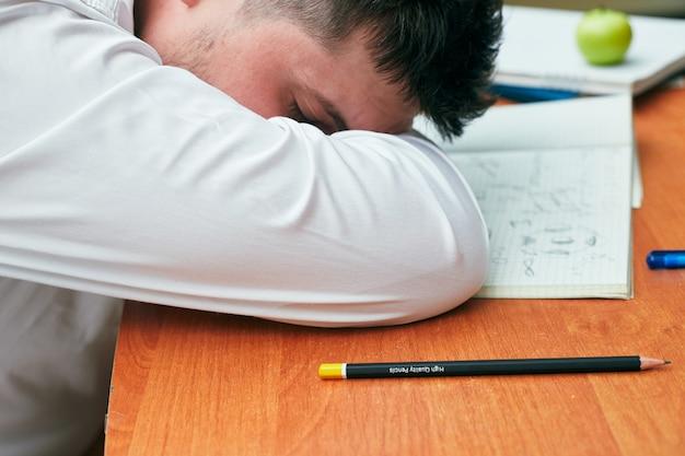 Un hombre durmiendo en una mesa con un cuaderno y un lápiz universidad, colegio