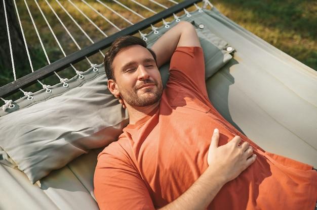 Hombre durmiendo una siesta en una hamaca en la naturaleza
