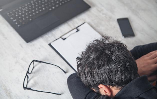 Hombre durmiendo sobre el lugar de trabajo en su escritorio
