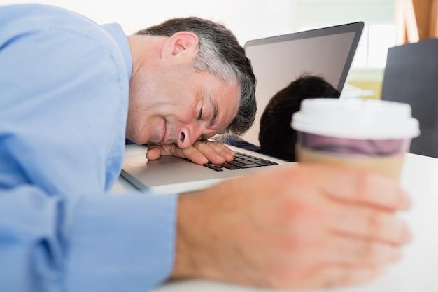 Hombre durmiendo en su laptop mientras sostiene café