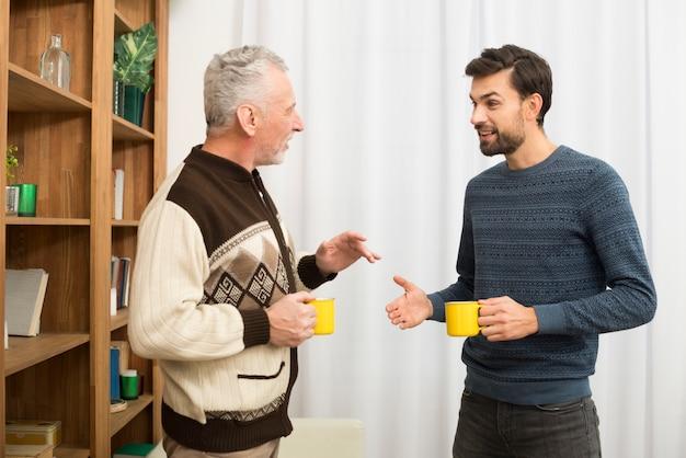 Hombre de edad y chico joven con tazas en la habitación.