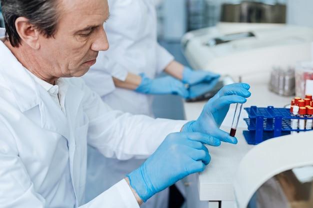 Hombre de edad. persona del sexo masculino confidente arrugando la frente y presionando los labios mientras está sentado en el laboratorio en posición semi