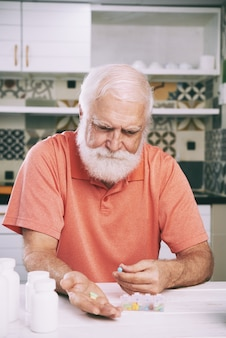 Hombre de edad tomando pastillas