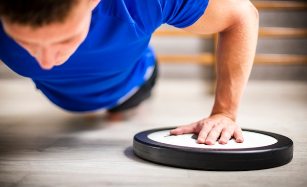 Hombre en ejercicio de flexiones de gimnasio