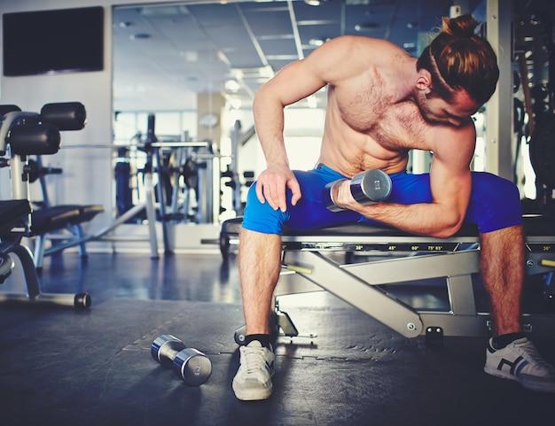 Hombre ejercitándose en la sala de pesas en el gimnasio