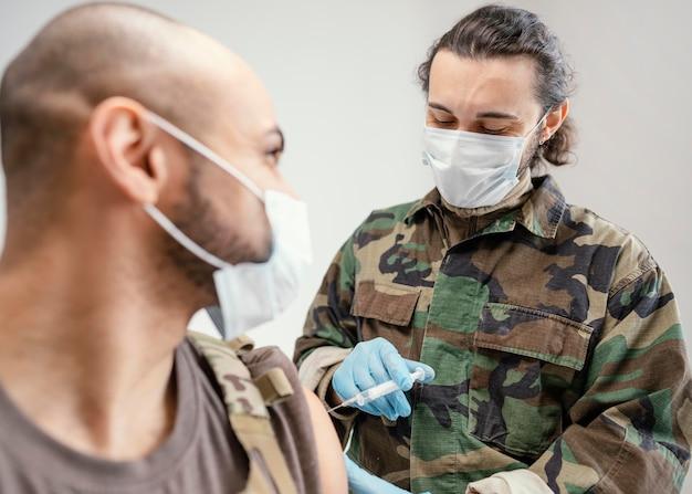 Hombre del ejército vacunándose