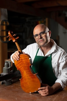 Hombre elaborando un instrumento en su taller.