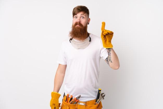 Hombre electricista pelirrojo con barba larga sobre pared blanca aislada apuntando con el dedo índice una gran idea