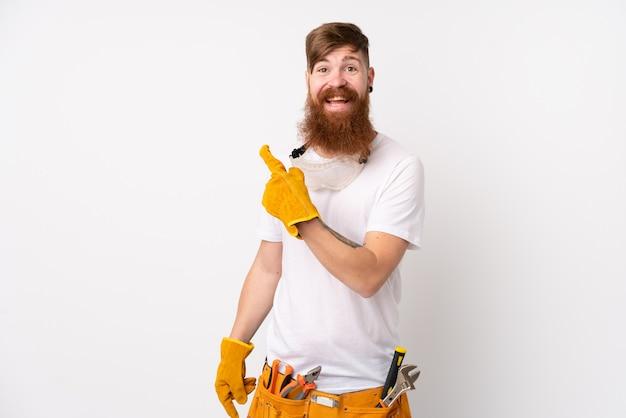 Hombre electricista pelirrojo con barba larga sobre la pared blanca aislada que señala el dedo hacia un lado