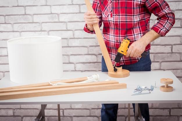 Hombre electricista que monta la lámpara de pie para la decoración del hogar