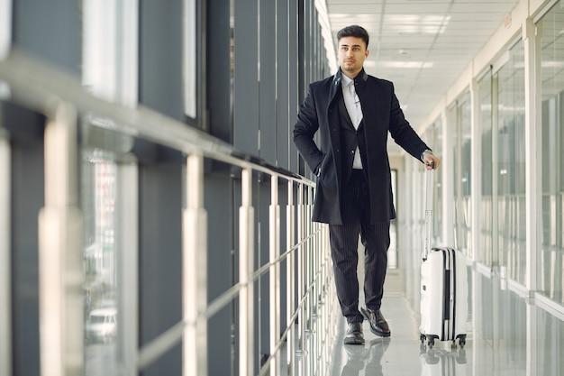 Hombre elegante en el aeropuerto con una maleta