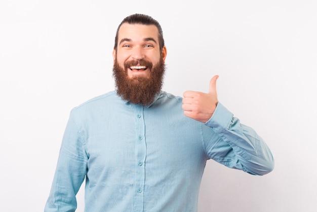 Hombre elegante alegre está mostrando el pulgar a la cámara.