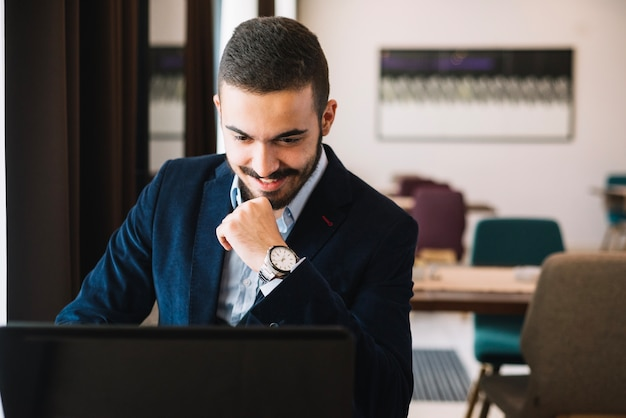 Hombre elegante alegre que usa la computadora portátil
