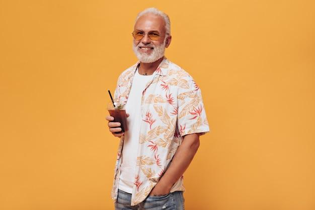 Hombre elegante en anteojos tiene cóctel para llevar en la pared naranja