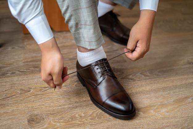 Hombre elegante ata los cordones de los zapatos de cuero.