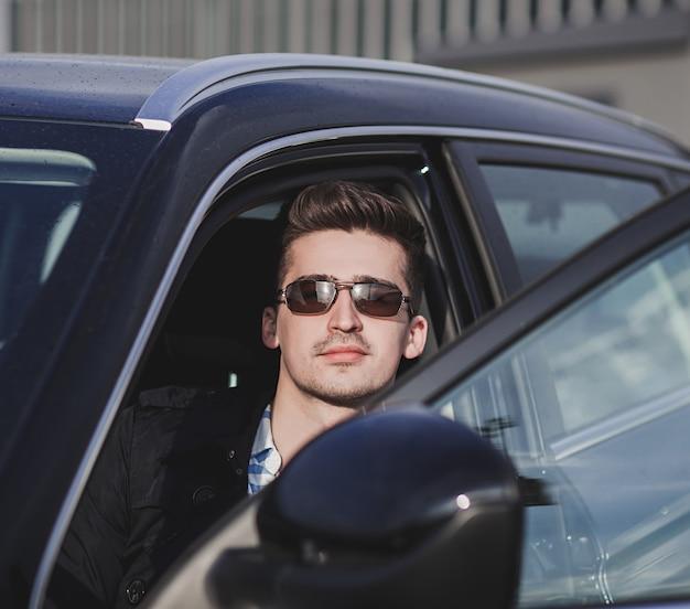 Hombre elegante atractivo en coche. hombre de negocios exitoso