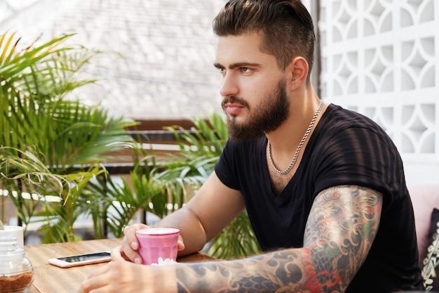 Hombre elegante barbudo sentado en la cafetería