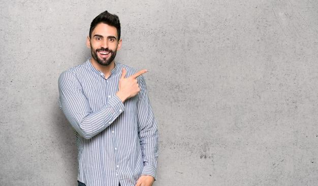 Hombre elegante con camisa apuntando hacia el lado para presentar un producto con textura de pared.